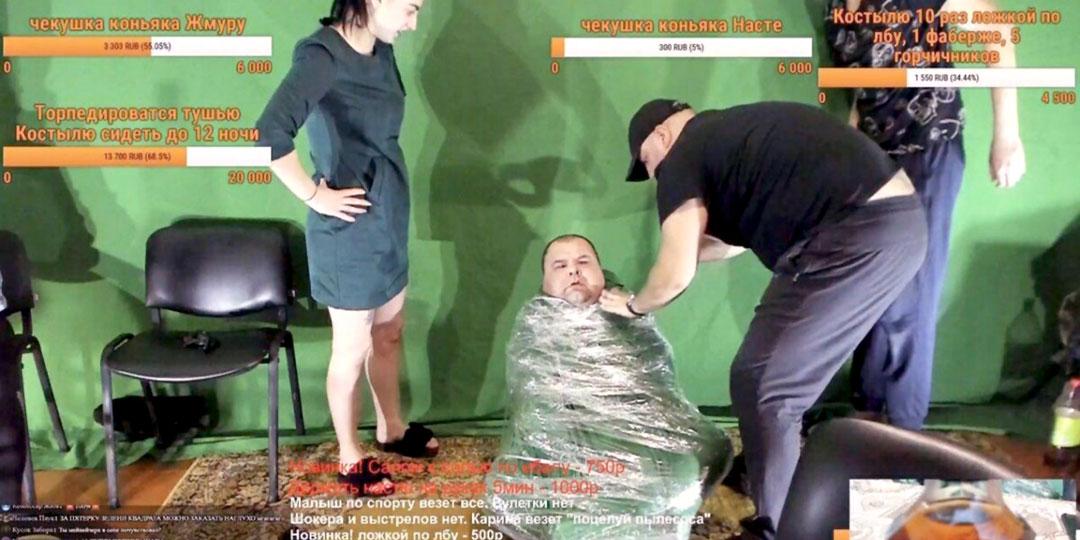 Кадр стрима с заданием обернуть человека в полиэтиленовую пленку. На мониторе можно разглядеть прейскурант других дурацких челенджей